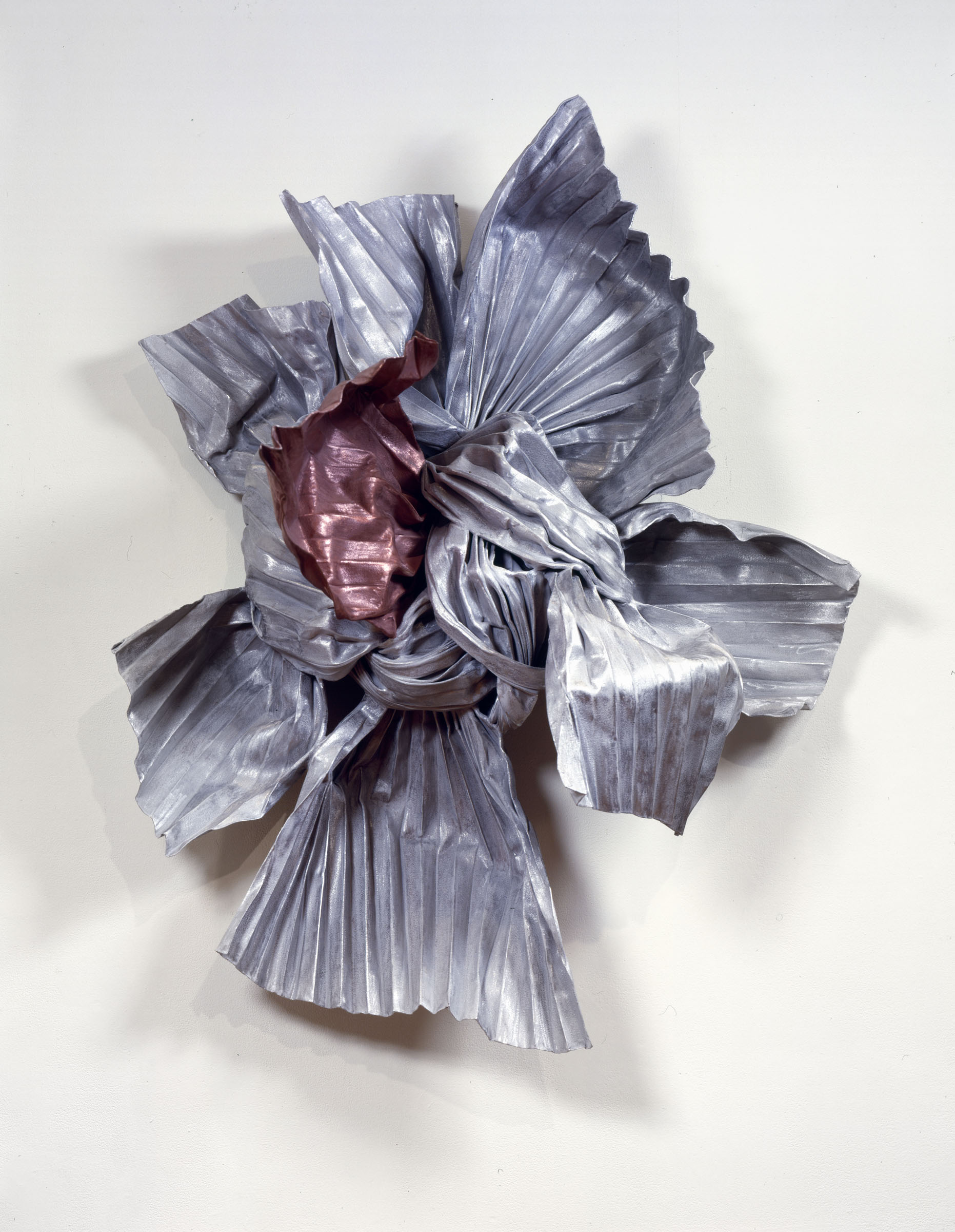Lynda Benglis's sculpture is a shining knot mounted on the wall made out of bronze, zinc, copper, aluminum, wire that has been manipulated to appear light as a bow.