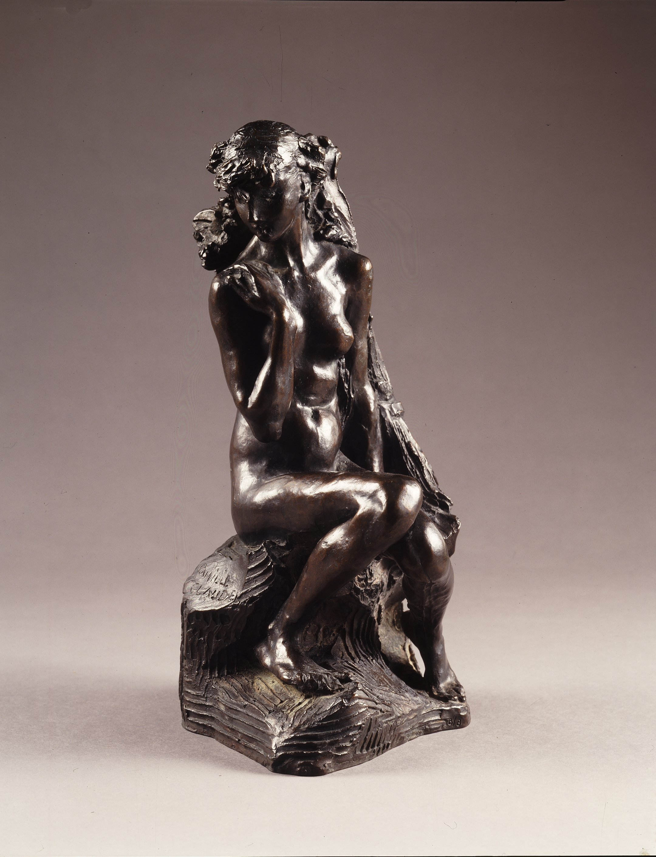 Camille Claudel's bronze sculpture depicting a naked young girl sitting on a rock with her left hand resting on her chest as she looks down toward the left.