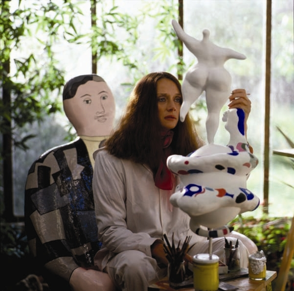 Niki de Saint Phalle sitting in a white jumpsuit painting the sculpture of a 'nana'.