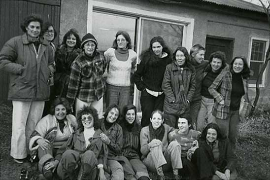 A black-and-white photograph of seventeen woman in front of a house. Seven of them are sitting in the front and the other ten are standing in a line behind.