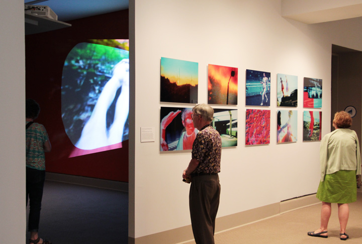 NMWA members looking at Rist's video installation and a series of her prints on Member Preview Day; Photo Laura Hoffman
