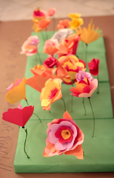 Guests contribute paper flowers to a collaborative floor installation