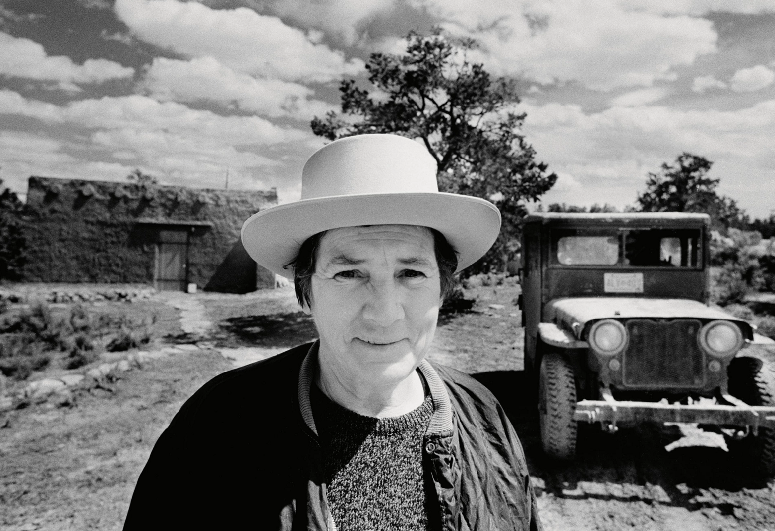 Black-and-white photograph of Agnes Martin standing on a dirt road; behind her are her adobe house, trees, and an old jeep. She is a light-skinned adult woman with short hair, seen from the bust up, wearing a jacket, sweater, and a white brimmed hat.