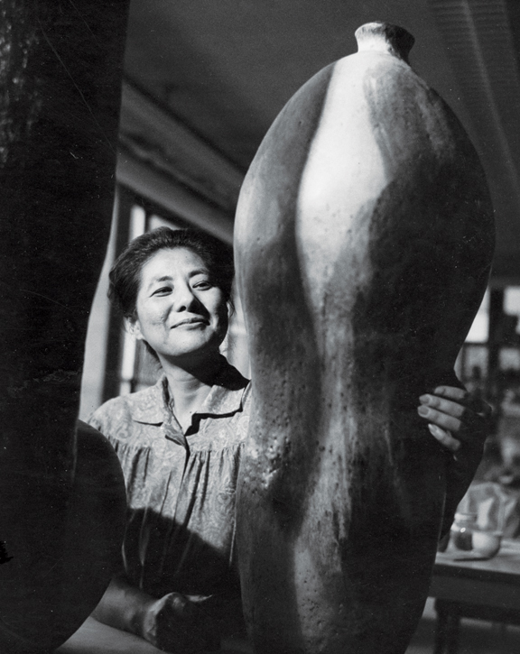 A black-and-white photograph of a light-skinned, dark-haired, Asian adult woman smiling while wearing a smock in her studio. In the foreground are two of her large sculptures; she has her hand on one of them.