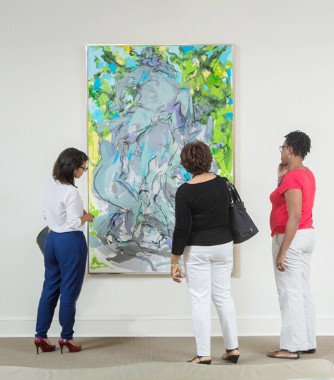 Three nicely dressed adult women stand and study a large, vertical, abstract painting on a white gallery wall. The painting suggests a central gray figure group in Bacchanalian revelry surrounded by vibrant green foliage and turquoise blue sky.
