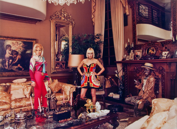 Two light-skinned adult women pose proudly in a luxurious brown living room overflowing with expensive looking furniture and items. The two women are blonde and wearing colorful, trendy outfits.