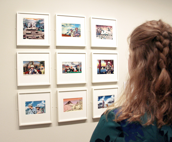 A visitor studies six of Hammam's photographs on view