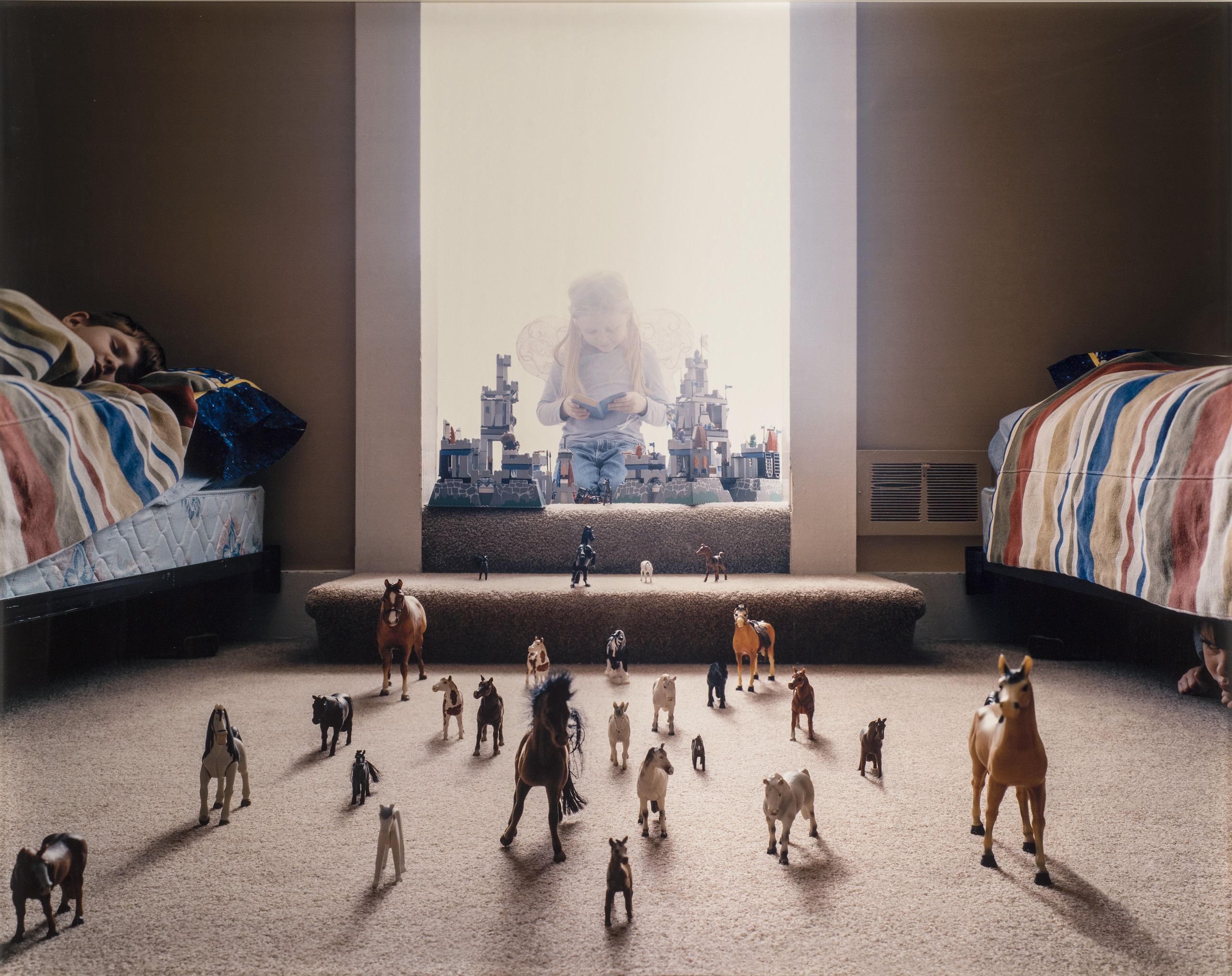 Three light-skinned children: one with long, blonde hair wears fairy wings and kneels, reading a book, behind a toy castle in a doorway full of light; one asleep on a bed on the left; and one under a bed on the right. Between the beds, dozens of toy horses stampede at the viewer.