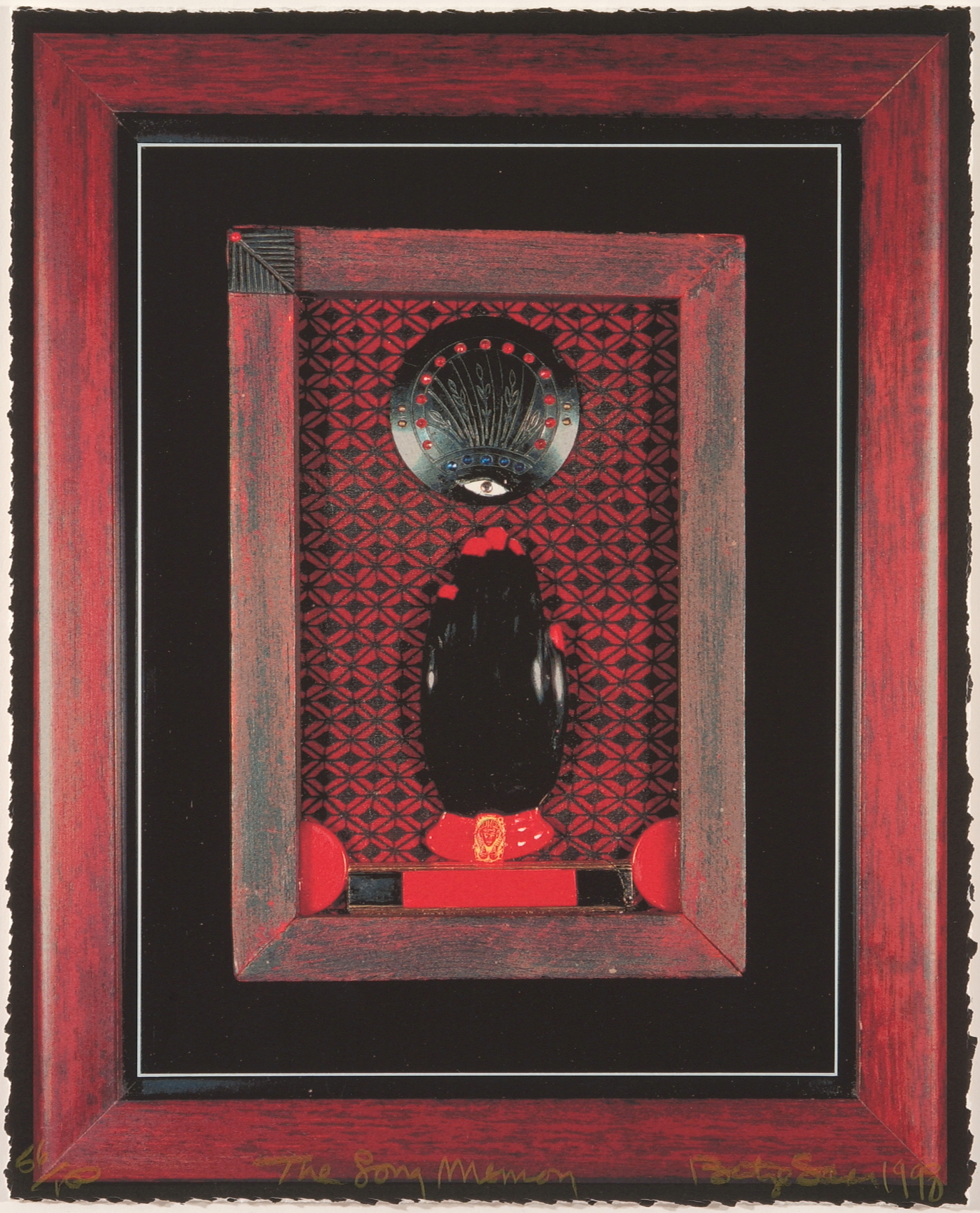 A black left hand with bright red nails and a red bracelet in a red wooden frame. It sits atop a black and red patterned background, fingers pointing toward a black medallion with an eye and other details. The red frame is surrounded by black and sits within a larger red frame.