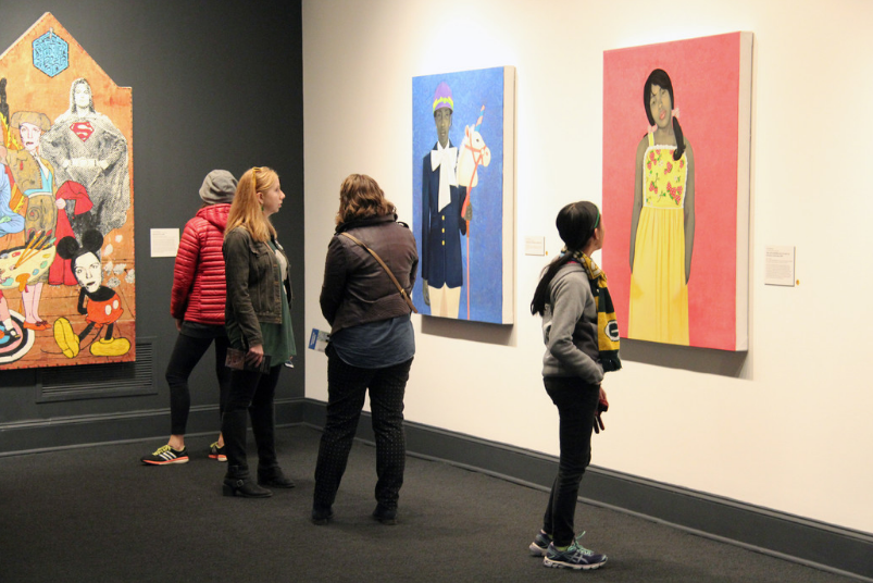 NMWA visitors look at Amy Sherald's paintings in a gallery.