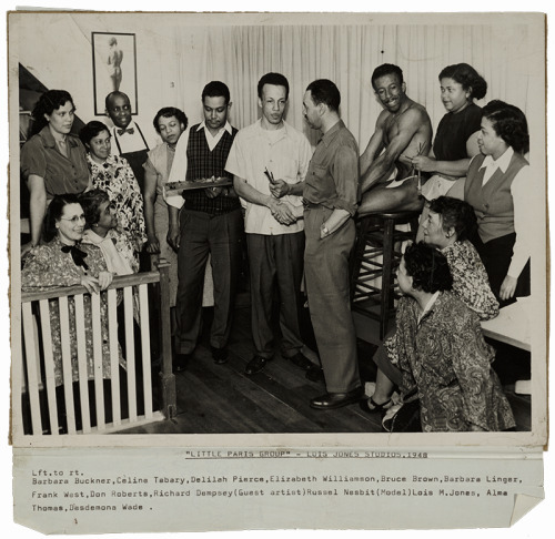 A black-and-white photograph of adult men and women in a homey room. They have a wide array of skin tones, though only one is light-skinned. Below the photograph is the caption Little Paris Group - Lois Jones Studios, 1948 with the names Barbara Buckner, Celine Tabary, Delilah Pierce, Elizabeth Williamson, Bruce Brown, Barbara Linger, Frank West, Don Roberts, Richard Dempsey (guest artist), Russel Nesbit (model), Lois m. Jones, Alma Thomas, Desdemona Wade.