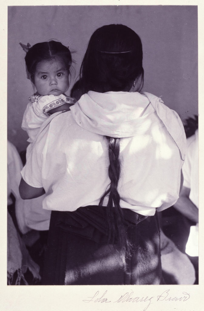 A black and white photograph of a woman, taken from behind her. Her long black braid trails down the center of her back, and she holds a young female child with chubby cheeks. The child looks directly at the camera from over the woman's left shoulder. The sleeves and collar of the child's white dress have floral borders.