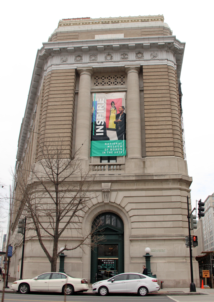 The exterior of NMWA—a tall, brown building with green doors, and a large banner down the side featuring Amy Sherald speaking in front of one of her paintings, the NMWA logo, and the word INSPIRE.