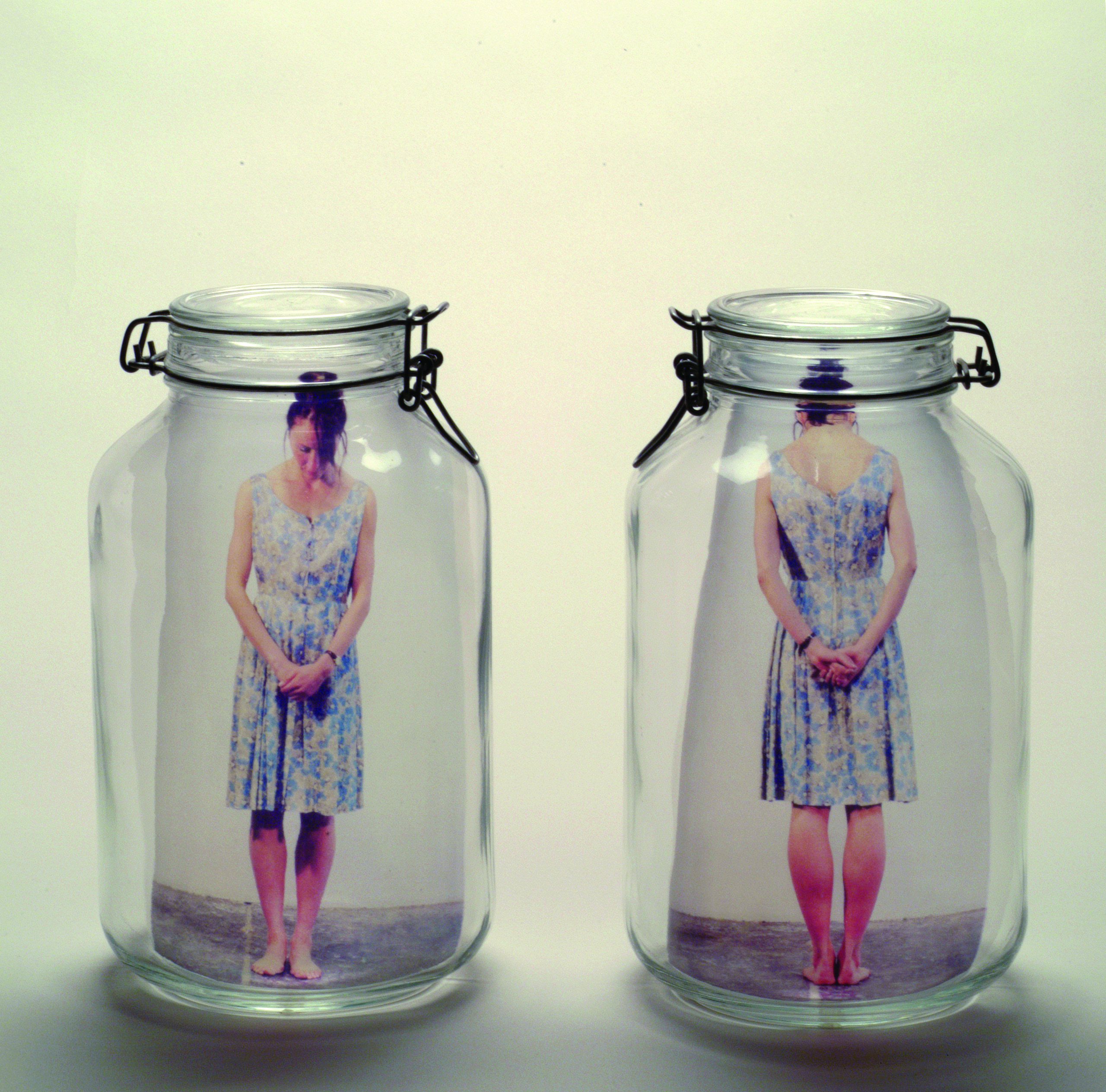 Two clear glass mason jars side by side. In the left jar is a color photograph of a light skinned woman standing with head bent and hands clasped in front of her. In the right jar is the same woman seen from rear with hands clasped behind her.