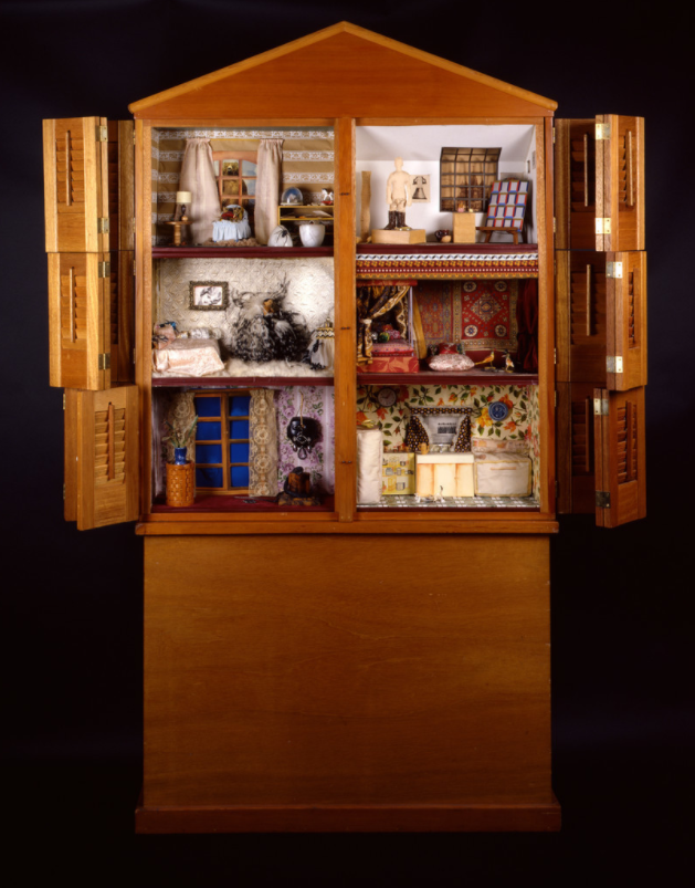 A tall wooden cabinet stands against a neutral black backdrop. Its doors are open to reveal a dollhouse interior made up of six rooms, each decorated with many different materials, including fabric and wood.