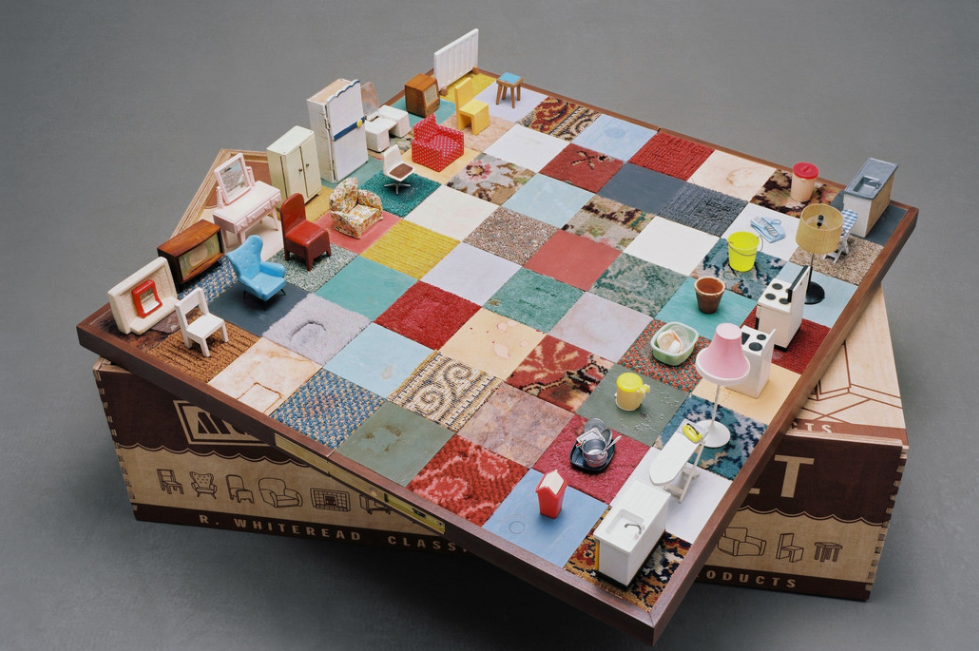 An object resembling a chessboard sits on top of a cardboard box in a neutral grey space. Rather than black and white squares, the chessboard is covered with fabric squares of many different patterns and textures. Rather than traditional chess pieces, the game pieces are miniature renderings of household objects like a washing machine, an armchair, and a vanity table.