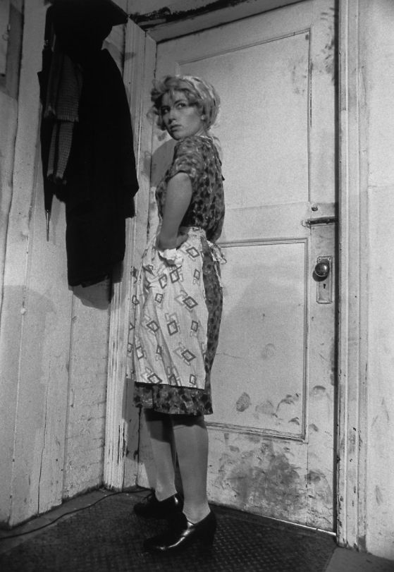 A black-and-white photograph of a light-skinned woman with light hair posing with her hand on her hip in front of a white door covered in dirt and scuff marks. She stands at a three-fourths angle and looks over her shoulder. She wears a patterned dress and apron. On the wall next to her hangs an umbrella and a dark coat.
