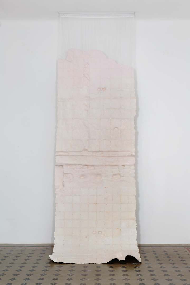 A long piece of fabric painted light pink and solidified with paper and glue hangs against a plain white wall. The paper and glue create a bumpy texture on the surface of the fabric that creates a grid-like pattern.