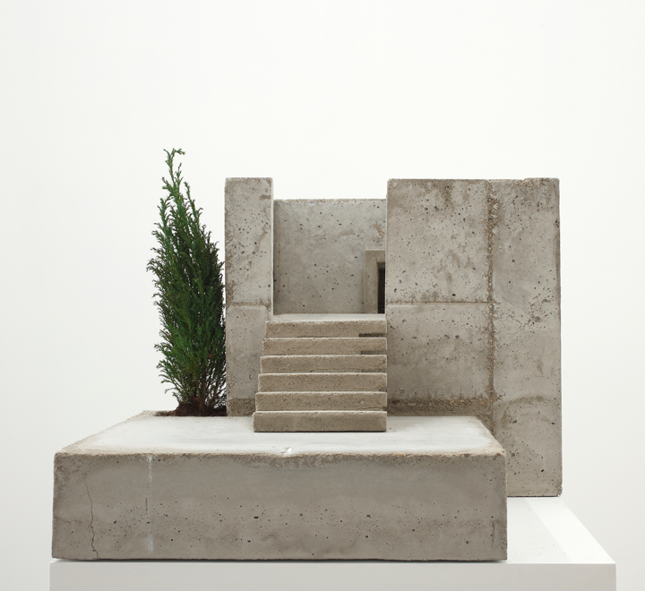 An architectural model made of concrete that represents the exterior and entryway of square-shaped building. The miniature structure sits on a white gallery display pedestal against a plain white background.