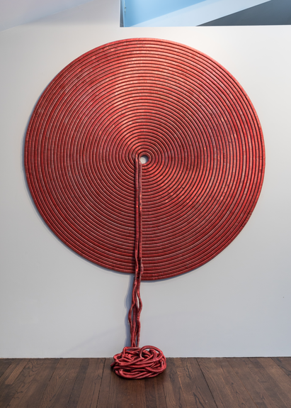A large, circular wall sculpture hangs on a plain white wall. This red-colored sculpture resembles wrapped yarn, with the loose ends spilling from the center of the sculpture to the floor.