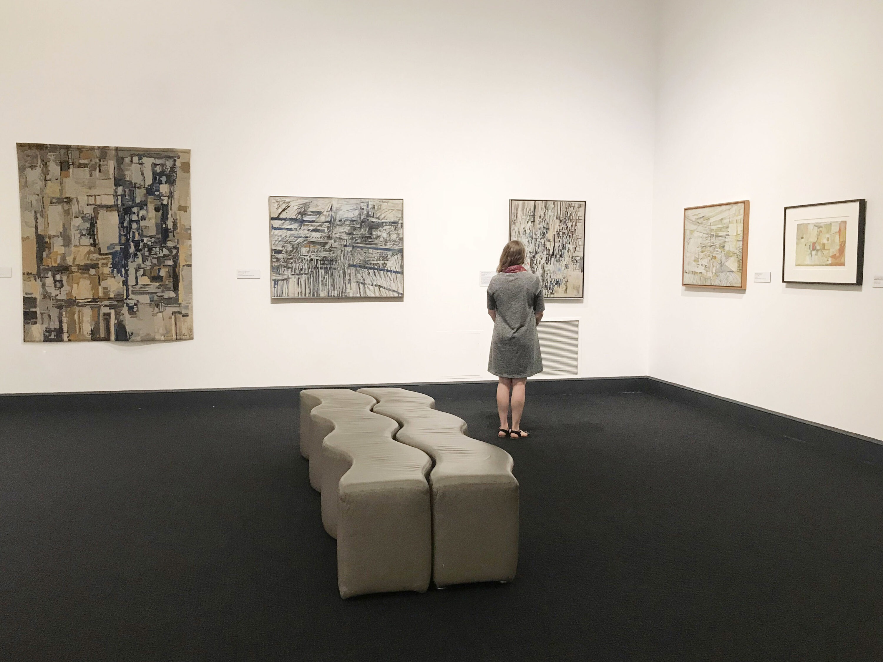 Large, abstract paintings that are light gray with black shapes and lines layered over them hang on white walls. The floor is dark gray and there is a light gray, squiggly bench. A light-skinned adult woman in a gray dress stands, looking at the paintings and away from the viewer.