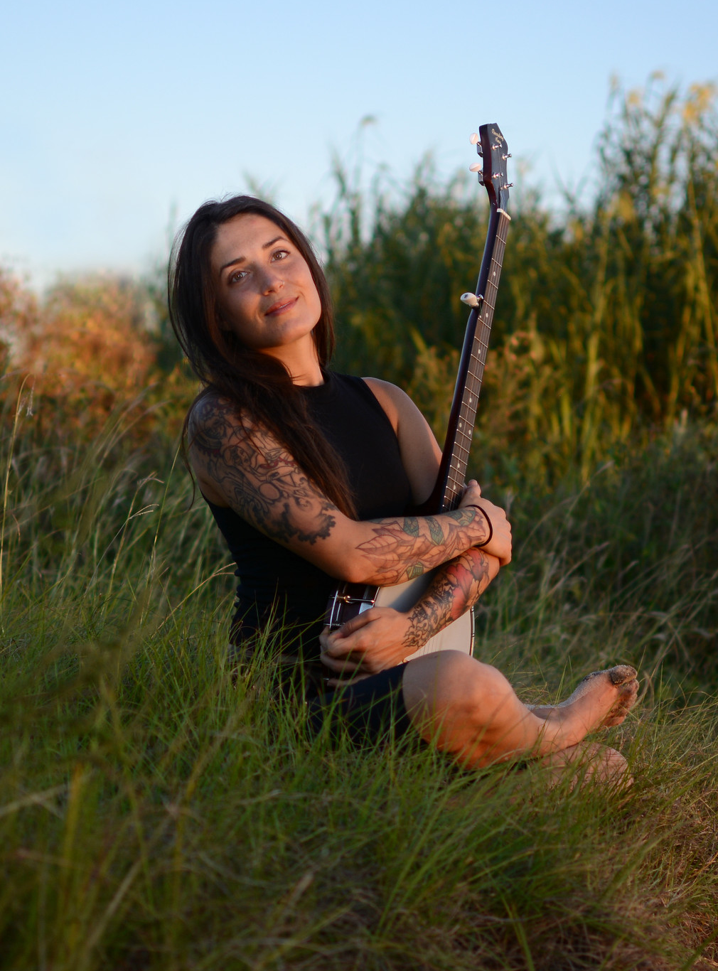 A light-skinned woman with dark hair sits cross-legged in a sunlit field, smiling at the camera. She wears a sleeveless black dress, showing off her colorful arm tattoos. In her lap, she holds a banjo.