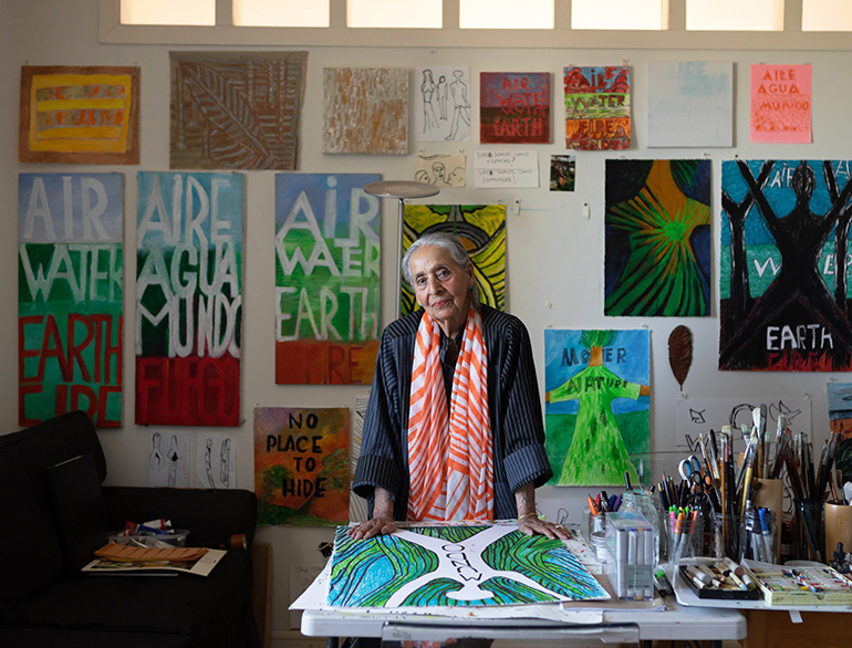 Luchita Hurtado stands in her home studio, surrounded by her paintings, many depicting scenes of nature.