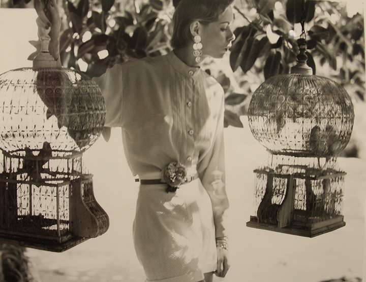 A sepia-toned photograph of a light-skinned, light-haired woman standing beneath a tree. A circular birdcage hangs on either side of her, each housing two small birds. The woman wears a white button-down blouse tucked into a pair of white shorts. She wears a thin belt with a fabric flower ornament attached to it. She wears large, geometric earrings and appears to be whistling to the birds in the cage on the right side of the photograph.