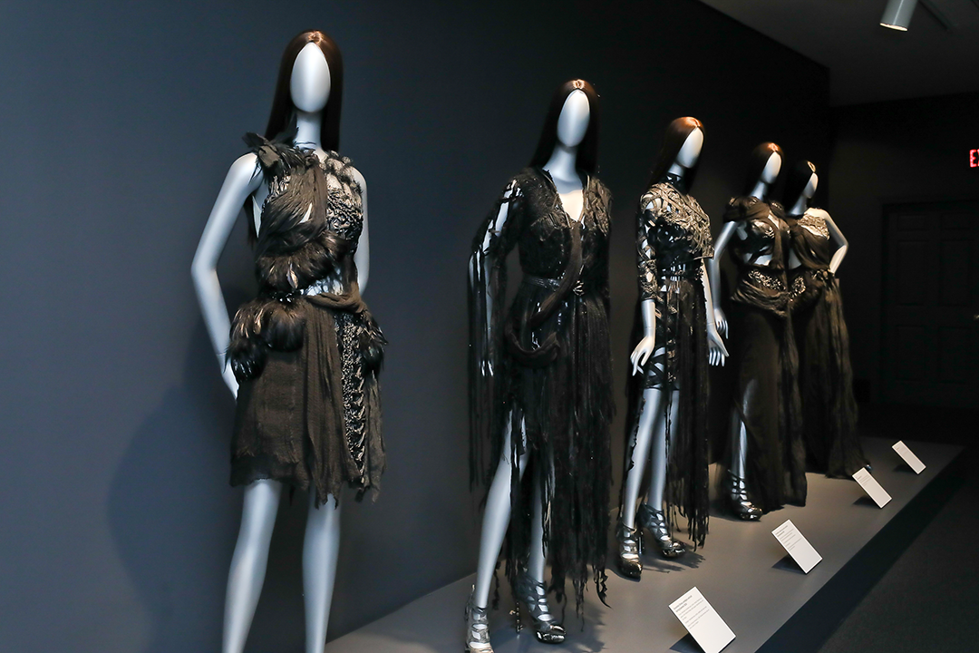 Five mannequins in a row wearing selections from Rodarte's Spring/Summer 2010 collection: black dresses made from distressed cheesecloth, leather, crystals, macramé, and plastic. The materials encase the figures in a loosely plaited network of pattern and texture.