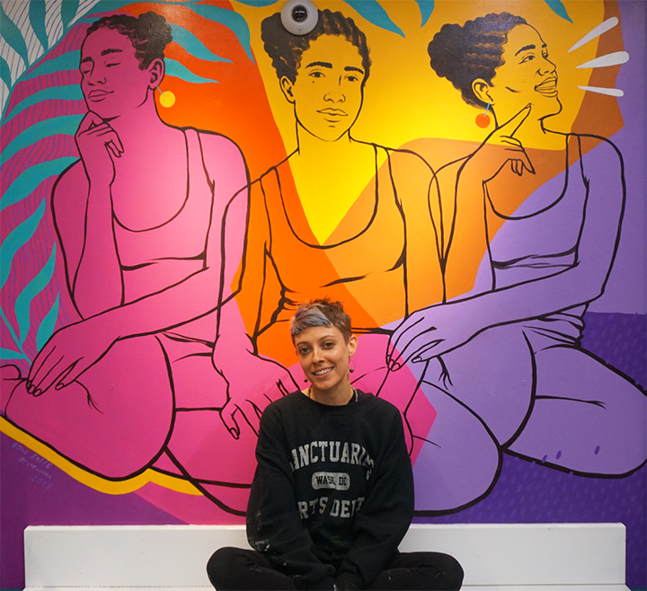 Rose Jaffe, a light-skinned woman with short, grey hair, sits in front of pink, yellow, and purple mural. The mural depicts three seated female figures with braided hair. Jaffe is dressed in an all-black outfit.