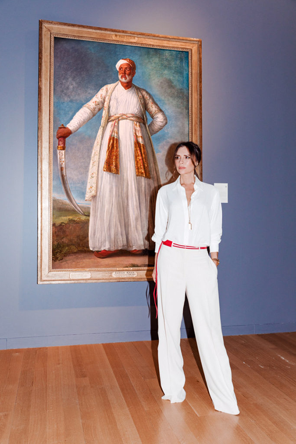 Victoria Beckham stands in a white jumpsuit with a red belt, in front of Élisabeth Louise Vigée Le Brun's Portrait of Muhammad Dervish Khan. Khan holds a sword, wears white, and looks powefully off into the distance.Beckham mimicks his pose.