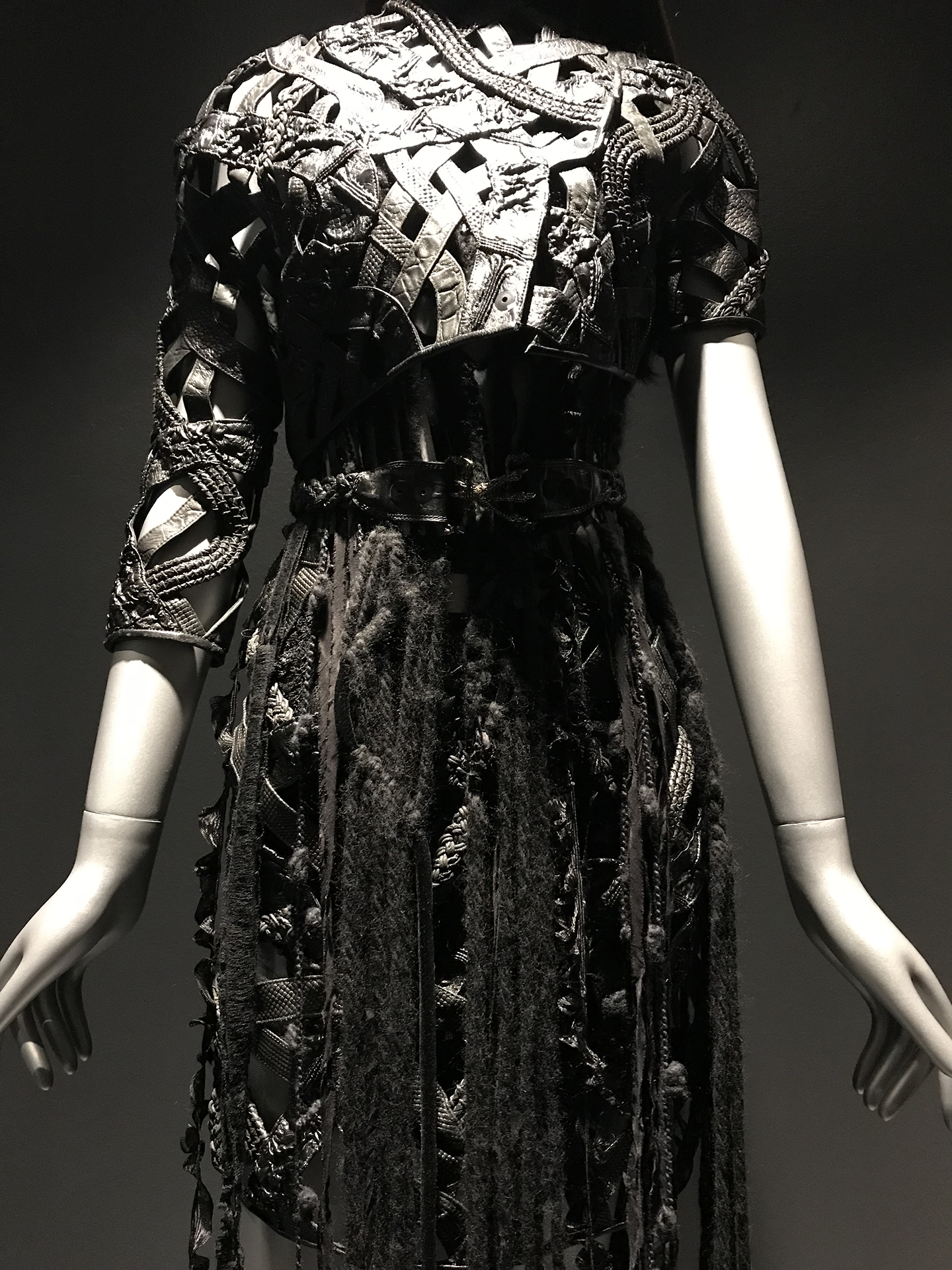 A close up of one of the black dresses, knee length, made of a leather and wool skirt, belt, and a leather top that is overlaid in a variety of patterns.