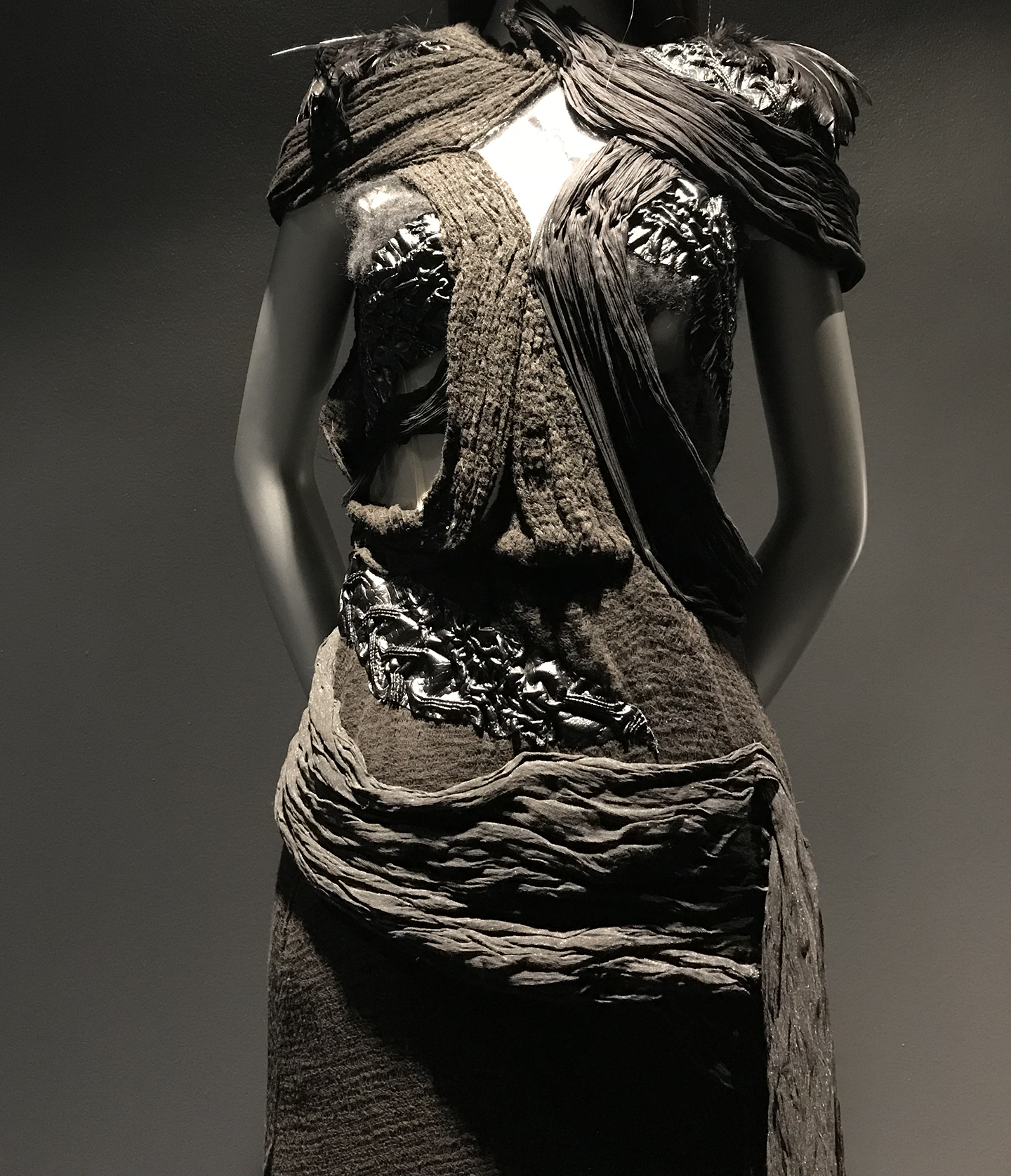 A close up of one of the mid-section of a black dress, made with nylon net,cotton cheesecloth, and pintucked and runched pleather and leather.