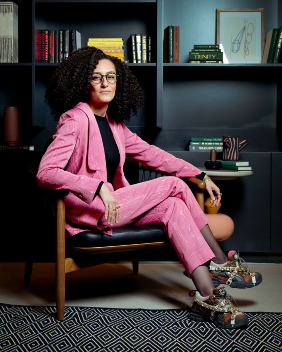 A portrait of United States Artists CEO Deana Haggag wearing a hot pink suit and jeweled, chunky soled Gucci sneakers.