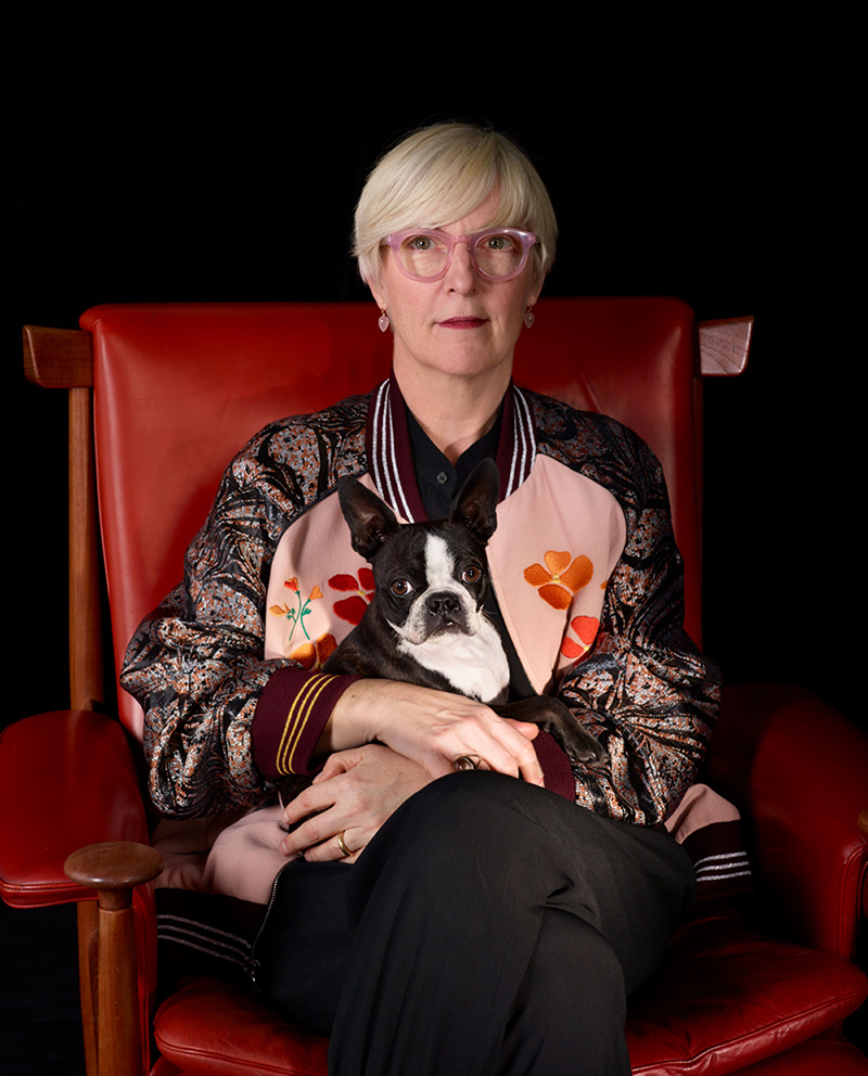 A portrait of curator Helen Molesworth, who wears a silk bomber jacket and holds her black and white pug in her arms, both staring straight at the camera.