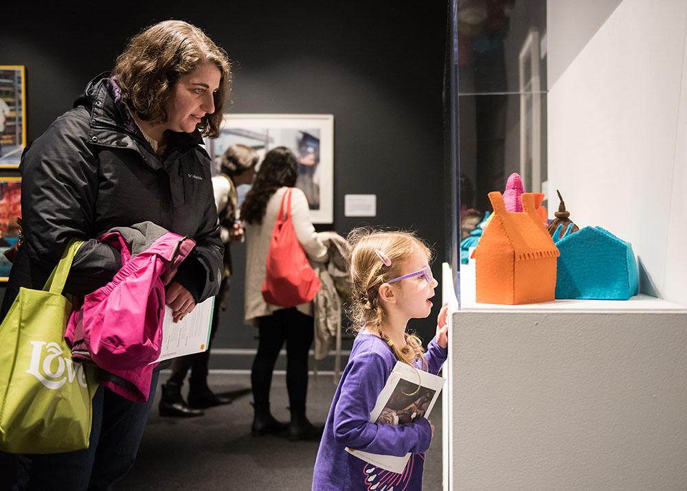 A young girl with her blond hair in a ponytail, wearing a purple shirt, and holding a NMA visitor's guide, looks excitedly at Laure Tixier's Plaid Houses (Maquettes). Her mother stands behind her also enjoying the work.