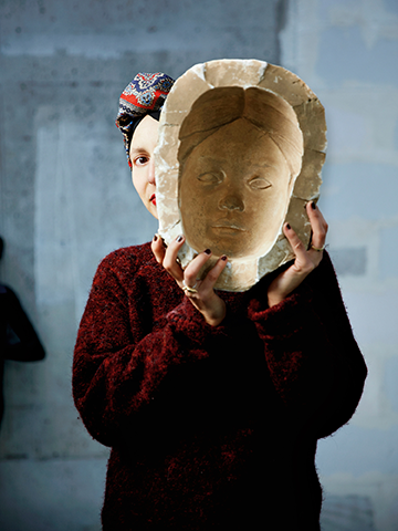 A portrait of a woman wearing a head scarf and red sweater, holding up a mask of, seemingly, her own face, made from plaster or clay. This is a promotional photo for the Doc Fortnight 2019 feature, Serendipity, directed by Prune Nourry.