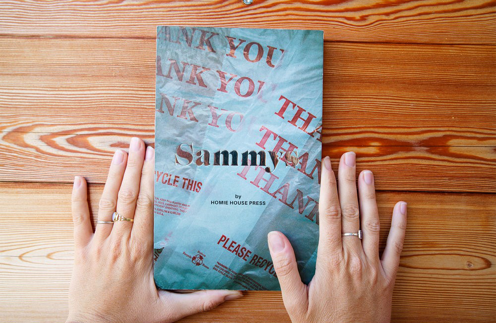 "Two hands frame the cover of a book that is titled ""Sammys"" and the cover is sandwich paper wrapping."