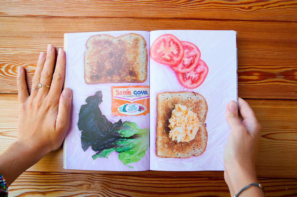 Two hands frame the Sammys book opened to a photo spread of a deconstructed sandwich including wheat bread, tomato slices, lettuce, and tuna fish.