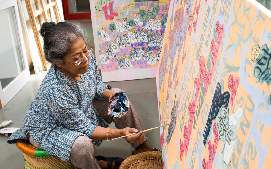 A photo of artist Arpita Singh painting in her studio. She holds a pallet of mixed blues and has her brush raised to the canvas.