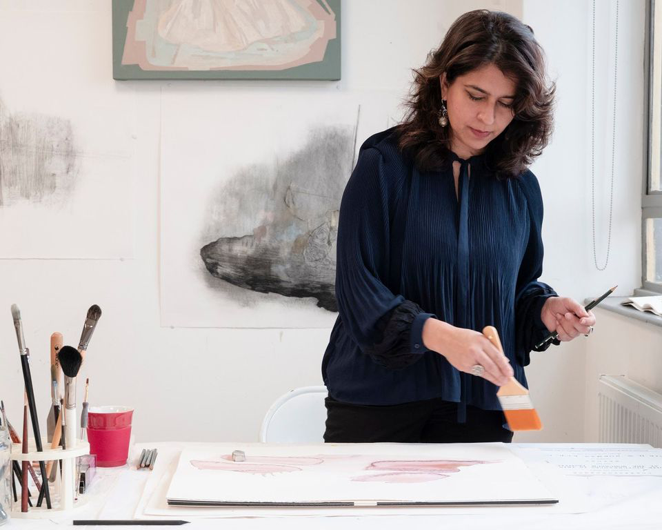 Artist Naiza Kahn wears a navy blue blouse and holds a paintbruch with orange paint on it over a canvas in her studio.
