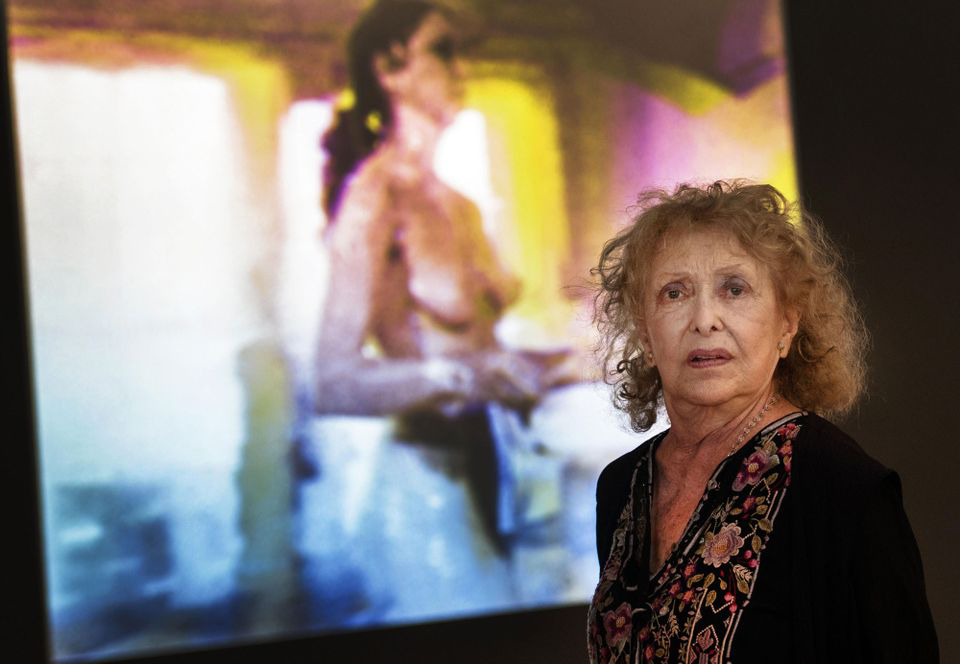 A photograph of Carolee Schneemann at age 78, staring candidly at the camera in front of one of her works--slightly blurred in the background, a topless woman seemingly holding something at waist level.