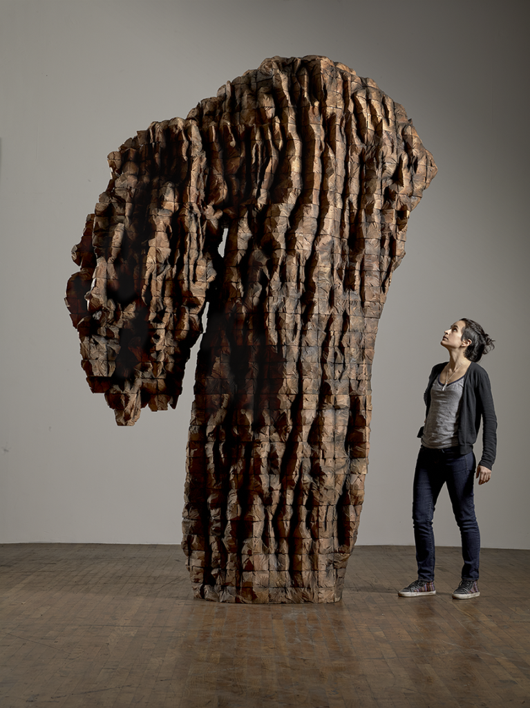 A woman stares up at a large and towering cedar sculpture that features a very tall base, perhaps 12 ft, with an extending smaller piece on the left that seems to hang down slightly, resembling the unevenness/organic makeup of a tree base.