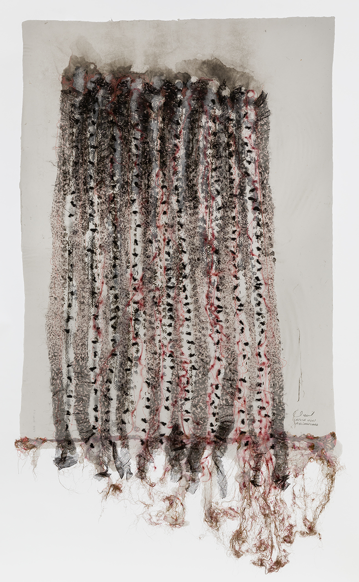 A gallery shot of a hanging work on paper, which includes uneven linear tendrils of red and black wool, thread, and pigment woven into the handmade paper. The materials seem to lift off of the paper, giving it a subtle sculptural quality.