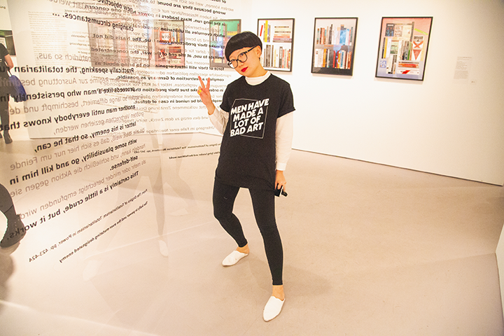 "JiaJia Fei stands in the center of a room of the Martha Rosler exhibition wearing black pants and a black tshirt that reads ""Men Have Made a Lot of Bad Art"" with her right hand up with peace fingers."