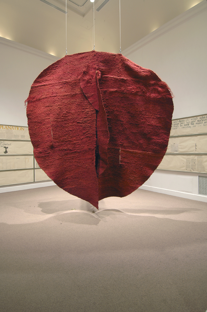 A large red, circular, sculpture of textured cloth hangs from the ceiling of a gallery.