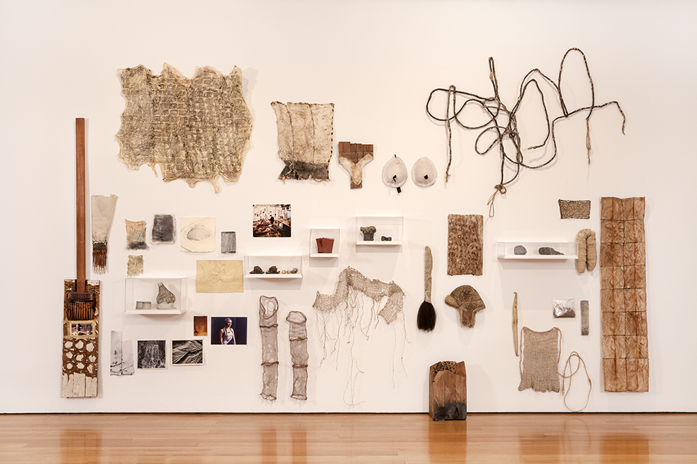 "A shot of a gallery wall that is hung with numerous items and oddities, part of Ursula von Rydingsvard's ""little nothings"" collection, including"" chiseled cedar objects, drawings on paper, copper wire costume sleeves with fake fingernails affixed at the ends, a broom, workshop tools, a bag of the artist's brother's hair, and more."