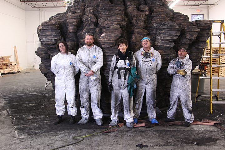 "A photograph of sculptor Ursula von Rydingsvard, center, who is surrounded by her four studio assistants--one woman, three men--as they stand in a large studio/warehouse space in front of her massive ""Bowl With Folds"" sculpture. The artist and her assistants all wear protective white jumpsuits, which are tarnished with graphite and two assistants have masks hanging around their necks."
