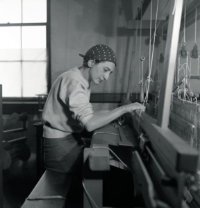 A black and white photo of artist Anni Albers at work in her studio. She wears a polka dot bandanna on her head and a plain white sweater. The photo is taken from the side of a loom, her hands are working the wood sections as she weaves.