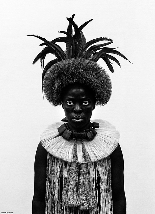 A black and white portrait of a very dark-skinned young person, staring straight at the camera, cropped at their torso. The person wears a chunky choker necklace on top of a broad straw collar with two large knots of rope hanging from it. Frond leaves grow from the top of their headdress.